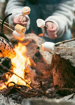 Giovane donna che brucia marshmallow nel fuoco di campo