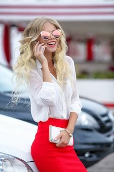 웃 고 휴대 전화에 선글라스에 젊은 여성 비즈니스 레이디