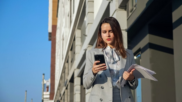 Young woman in a business suit with a phone and documents walking down the street.