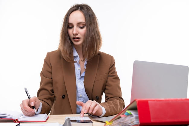 A young woman in a business suit working at a desk