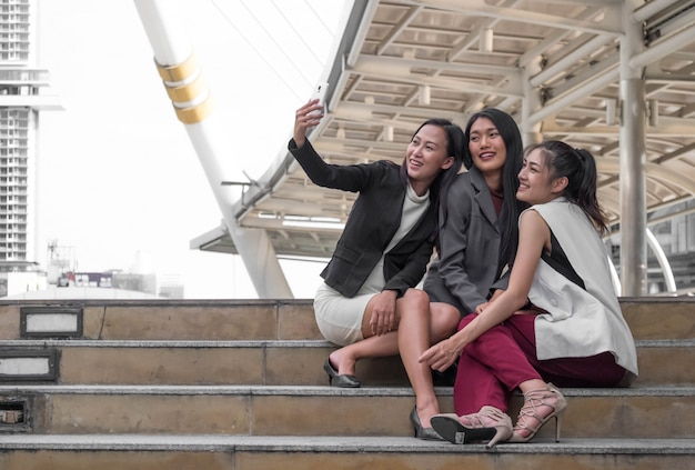 Young woman business team outdoors setting taking a selfie