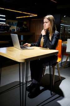 Бизнесмен молодой женщины, сидя за столом, работающим с ноутбуком. девушка-менеджер в офисе работает над новым проектом