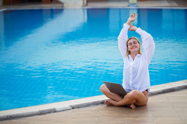 Young woman businessman with laptop sitting by the pool. open workplace. freelancer concept. online shopping. vacation work