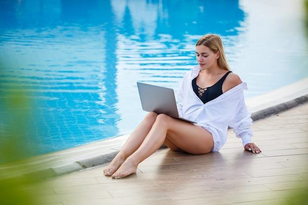 수영장 옆에 앉아 노트북으로 젊은 여성 사업가. 열린 직장. 프리랜서 개념입니다. 온라인 쇼핑. 휴가 일