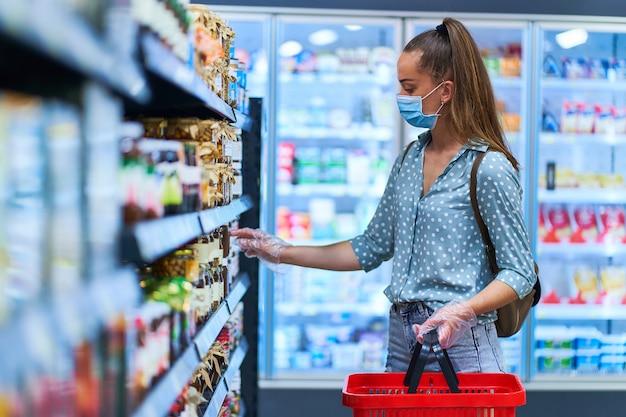 防護マスクと買い物かご付きの透明な手袋の若い女性バイヤーは、食料品店で製品を選択します