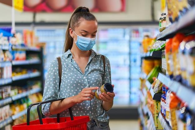 医療用防護マスクを身に着けている若い女性バイヤーは食料品店で食品を選択します