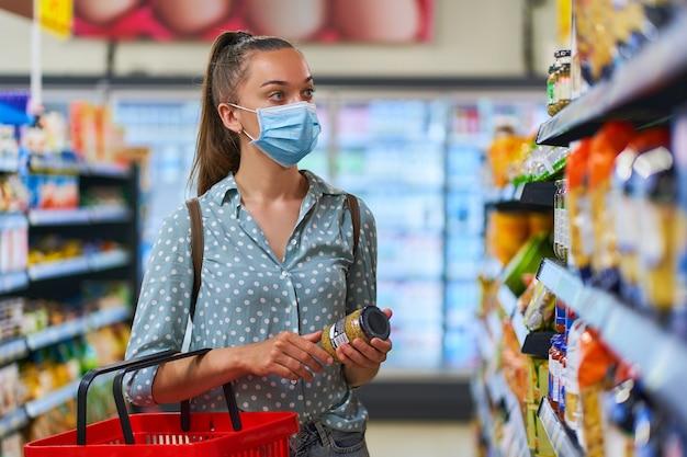 ショッピング棚の中で医療用防護マスクを着ている若い女性バイヤーは、食料品店で食品を選択します