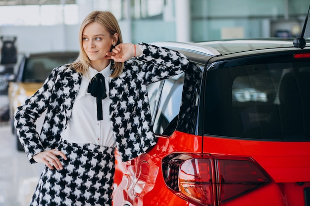 Young woman buying a car in a car showroom