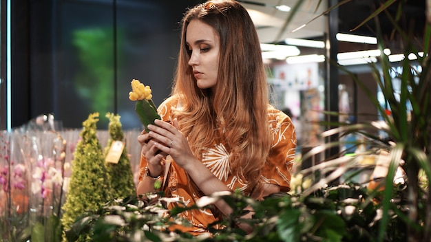 園芸用品センターで鍋に花を買う若い女性