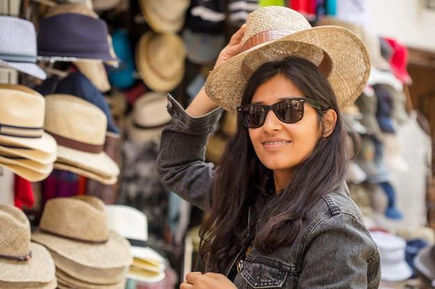 Young woman buying hats