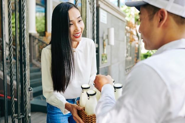 Молодая женщина покупает молоко