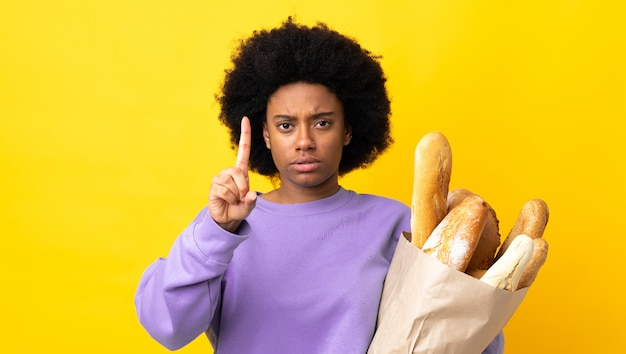 Young woman buying some bread over isolated background