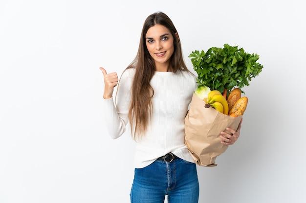 Молодая женщина покупает еду, изолированную на белой стене, указывая в сторону, чтобы представить продукт