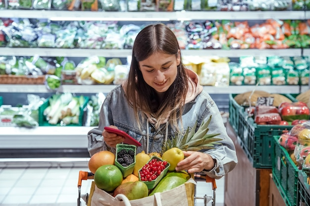 A young woman buys groceries in a supermarket with a phone in her hands