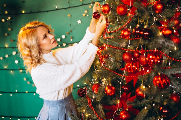Young woman by the christmas tree on christmas