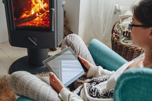 Young woman by the fireplace, sitting in a cozy armchair, with a warm blanket, using a tablet