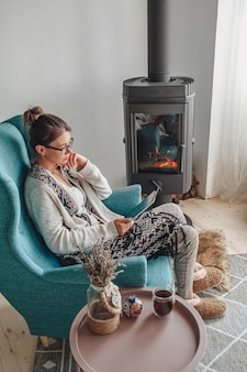 Молодая женщина у камина, сидя в уютном кресле, с теплым одеялом, с помощью планшета