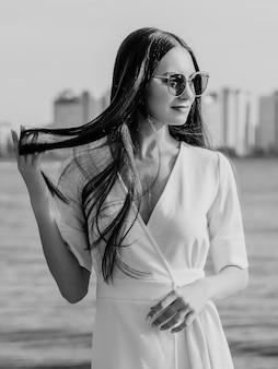 강 젊은 여자. 도시 경관. 하얀 드레스를 입고 갈색 머리입니다. 긴 머리. 아름다움과 패션. 선글라스에 소녀입니다. 흑백 사진