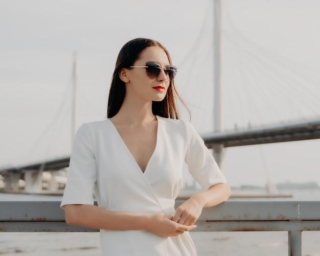 川沿いの若い女性。都市景観。白いドレスを着たブルネット。長い髪。美しさとファッション。サングラスの女の子