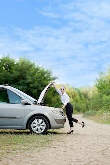 車が故障した道端の若い女性ボンネットを開けて被害を確認