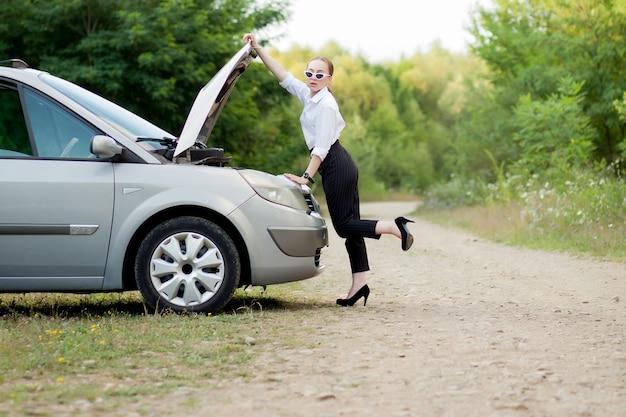 Молодая женщина на обочине дороги после того, как ее машина сломалась
