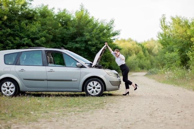 車が故障した後の道端の若い女性