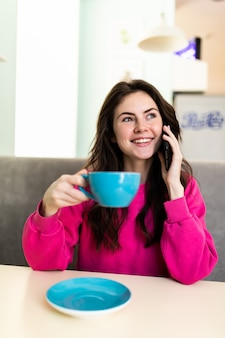 Young woman at cafe drinking coffee and talking on the phone