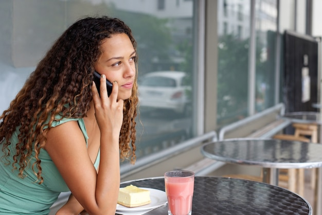 Young woman at cafe making a phone call