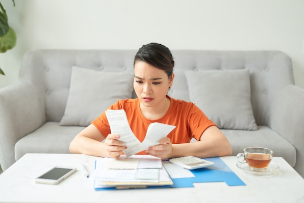 Young woman calculates monthly expenses