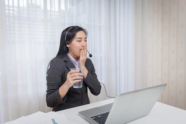 Молодая женщина оператор call-центра, сонливость на работе.
