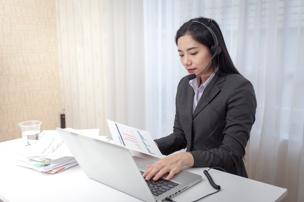 Young woman call center operator working in office. service desk consultant talking.