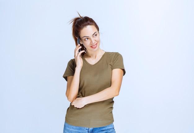 彼女のパートナーを呼び出し、電話に話している若い女性