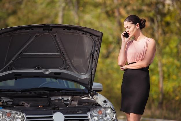 Молодая женщина, вызов в службу эвакуации. ее машина сломалась на дороге.