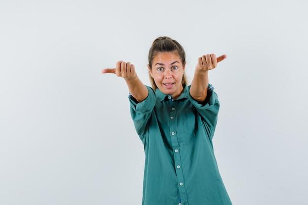 青いシャツを着て手振りで誰かを呼び出し、準備ができている若い女性