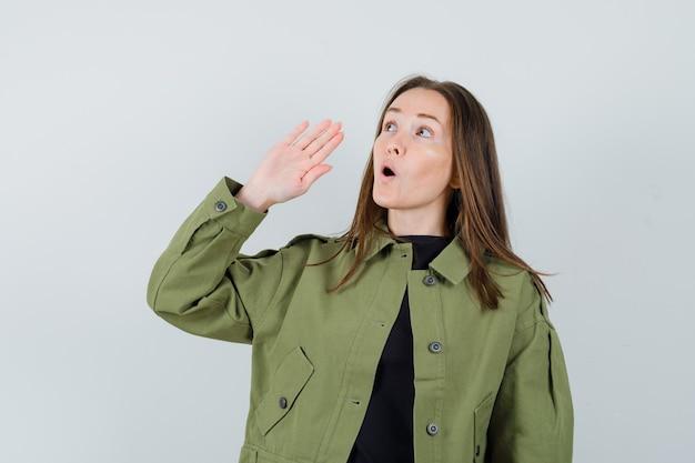 녹색 재킷에 시끄러운 목소리로 누군가를 호출하고 집중 찾고 젊은 여자. 전면보기.