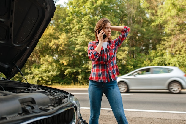Young woman calling a tow truck on road, car breakdown. broken automobile or emergency accident with vehicle, trouble with engine on highway