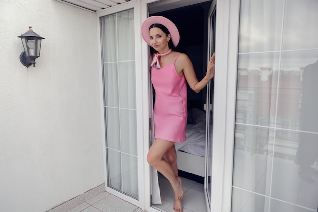 若い女性はホテルでの休暇中にピンクのショートドレスと帽子の高い白い窓のあるバルコニーに出てきました