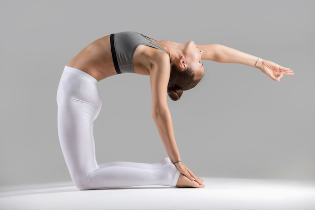 Young woman in camel pose, grey studio background