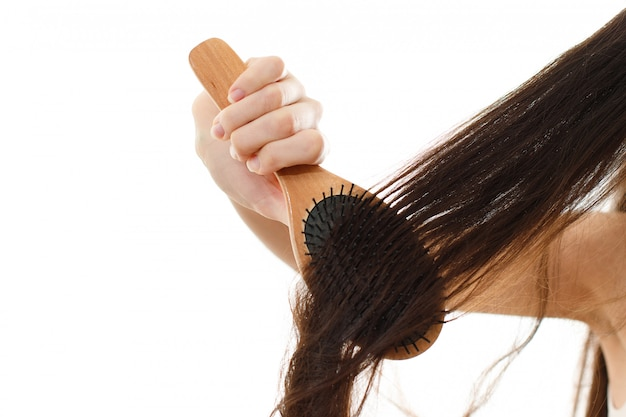 A young woman can not comb out the problematic tangled hair. on white isolated close up