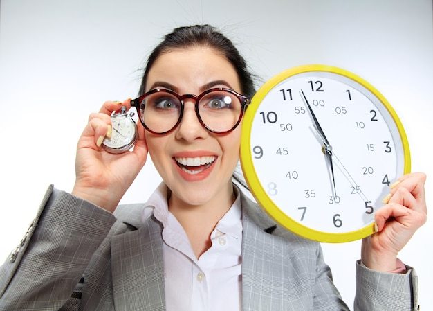 Young woman can't wait to go home from the nasty office. holding the clock and waiting five minutes before the end. concept of office worker's troubles, business or problems with mental health.