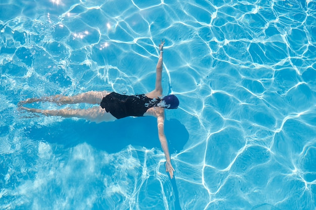Young woman in cap sports swimsuit swimming underwater in blue outdoor pool