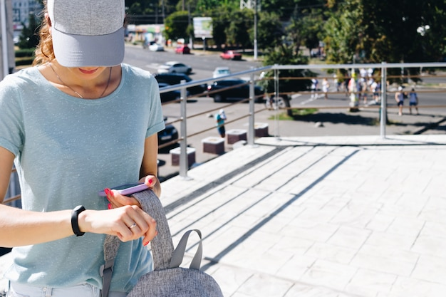 Young woman in cap and with a backpack synchronizes data with smart watches and phone