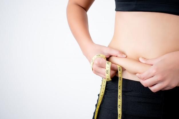 Молодая женщина фиксирует лишний жир на животе с помощью измерительной ленты