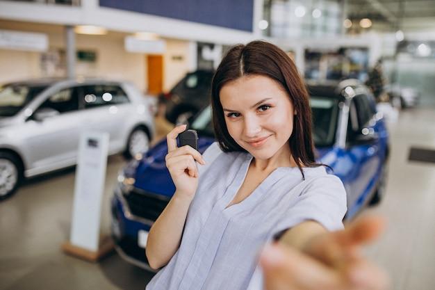 Young woman in a car showroom choosing a car