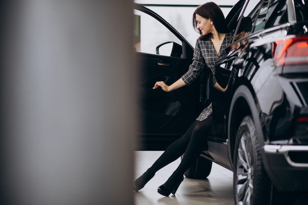 Young woman in a car showroom choosing a car