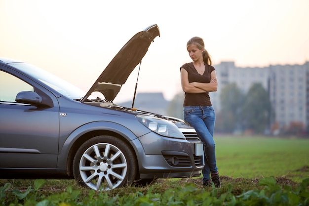 Young woman and a car with popped hood.
