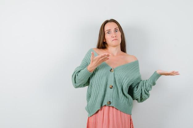 Giovane donna in cardigan, gonna che mostra gesto di benvenuto e guardando perplesso, vista frontale.
