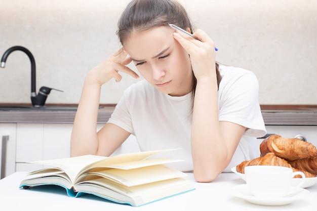 Молодая женщина внимательно читает книгу, думает, сосредоточена