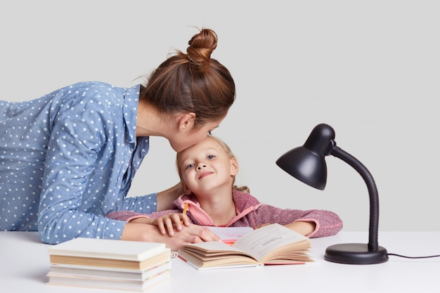 Young woman cares of her child, kisses daughter in forehead, praises her to study well, explains material, read books and prepare for lessons at school, isolated on white. studying concept