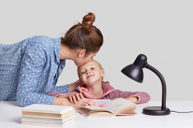 若い女性は彼女の子供の世話、額に娘にキス、彼女をよく勉強することを称賛し、資料を説明し、本を読み、白で隔離され、学校でのレッスンの準備をします。勉強のコンセプト